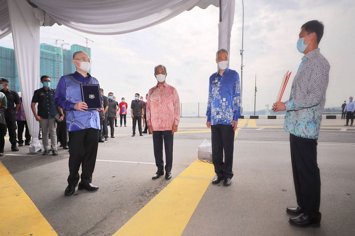 (From left) Malaysian Transport Minister Wee Ka Siong, Malaysian Prime Minister Muhyiddin Yassin, Prime Minister Lee Hsien Loong and Transport Minister Ong Ye Kung at the international boundary line on the Causeway on July 30, 2020. Singapore and Mal