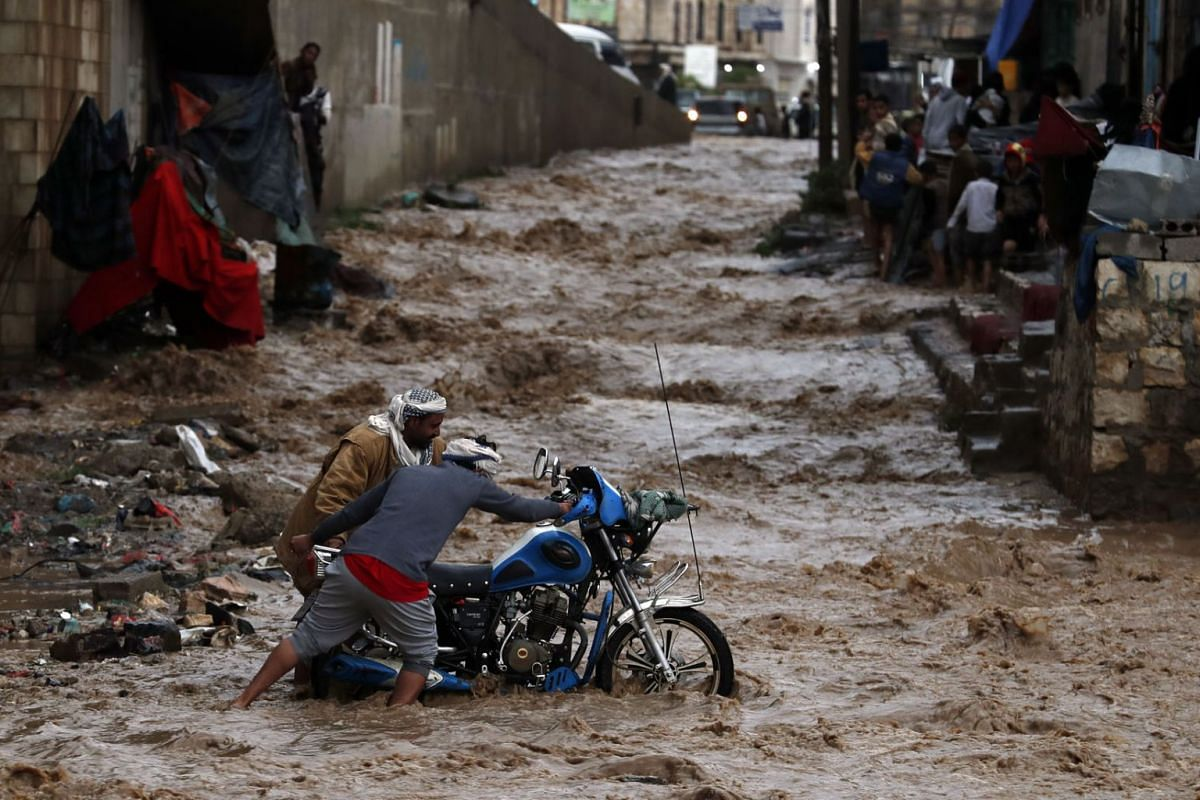 Yemenis attempt to get a motorcycle out of floodwater caused by heavy rainfall in Sana'a, Yemen, July 29, 2020. PHOTO: EPA-EFE