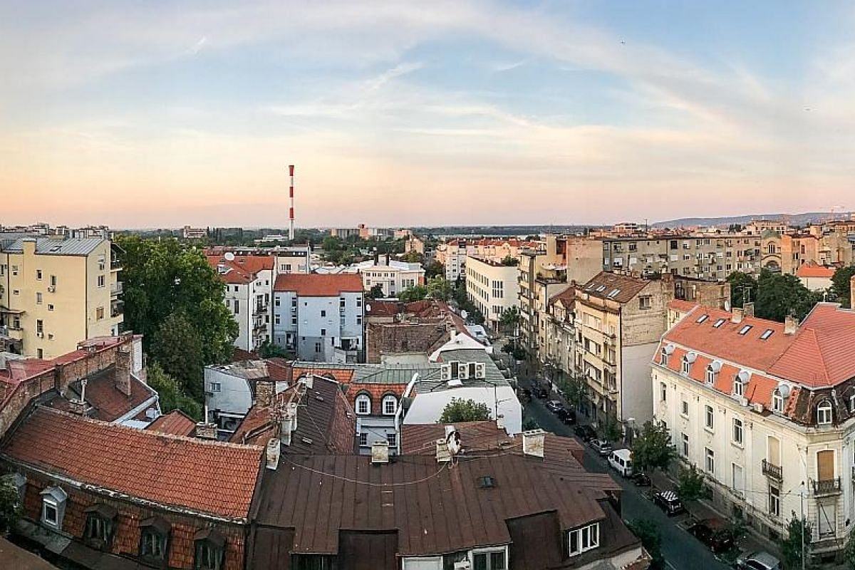 The writer and her boyfriend David Henden. The view from the rooftop of the writer's apartment, featuring Belgrade simmering in the summer sun. (Above, left) The transit hall felt surreal as the morning light sliced through the severe mood of the Doh