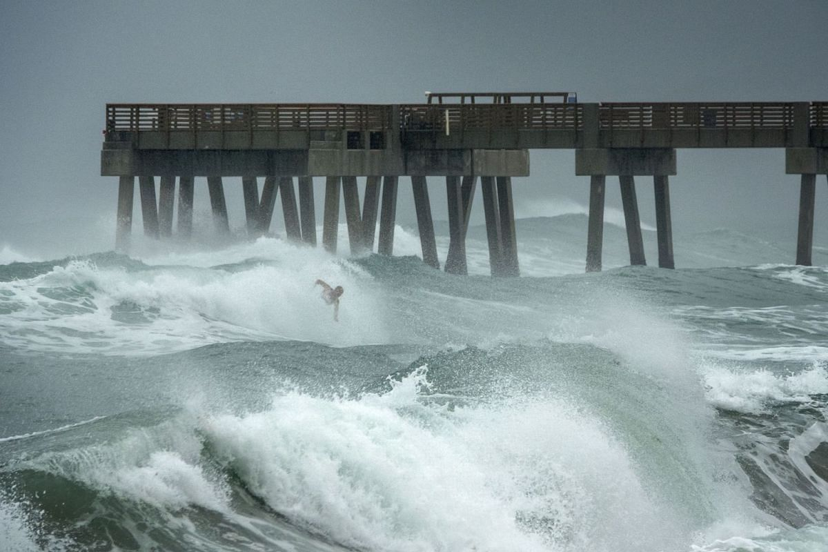 A surfer braves the high waves at Juno Beach Pier in Juno Beach, Florida, USA on August 2, 2020, as tropical storm Isaias passes near the Florida shores. PHOTO:  EPA-EFE