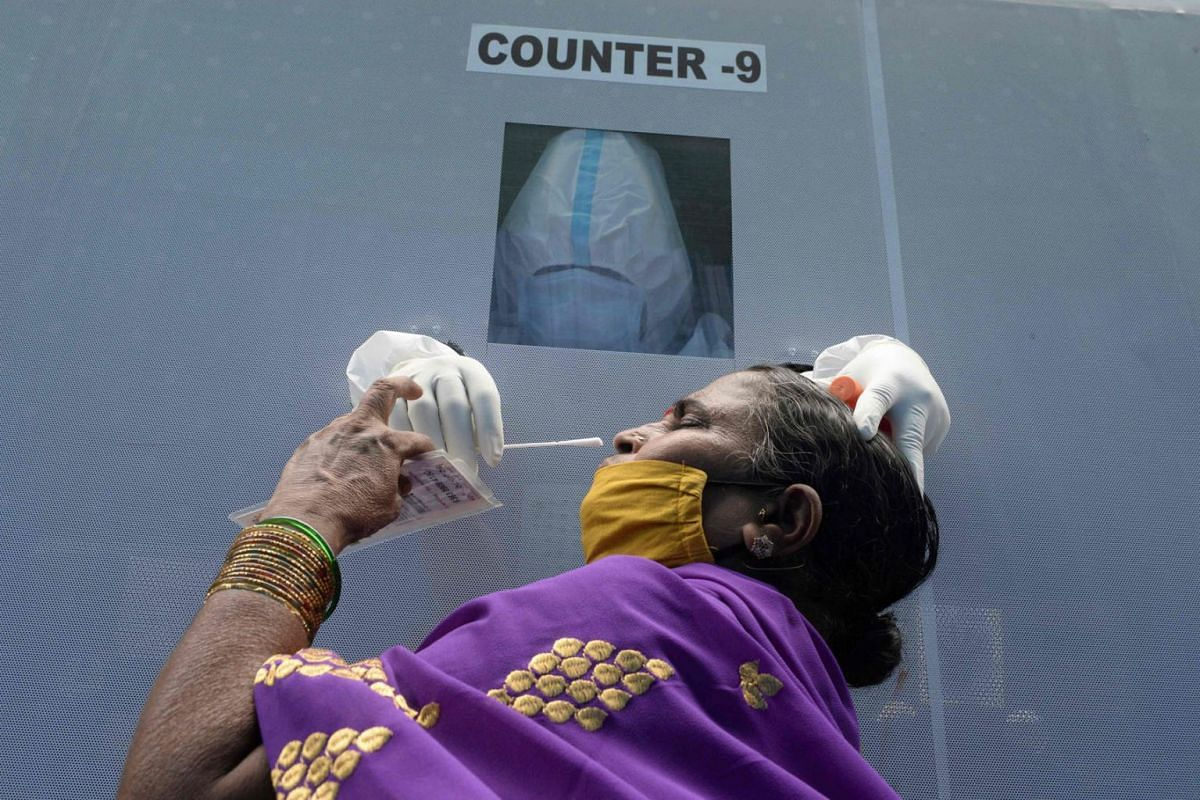 A health worker wearing Personal Protective Equipment (PPE) suit sits inside a mobile testing bus while collects a swab sample from a resident for a free coronavirus test in Hyderabad on August 3, 2020. PHOTO: AFP