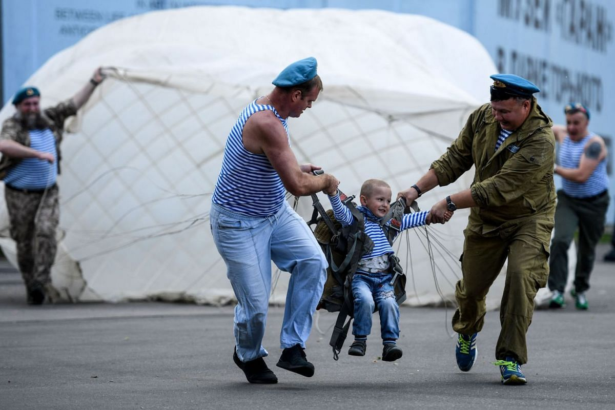 Russian airborne veterans entertain a child with a parachute as they celebrate the 90th anniversary of the establishment of Russia's airborne forces during the Paratroopers' Day at Gorky park in Moscow on August 2, 2020. PHOTO:  AFP