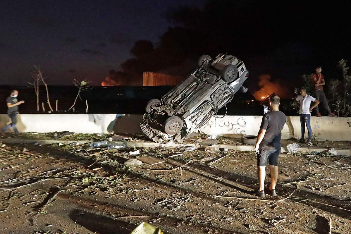 People gather by cars destroyed following an explosion at the port of Beirut on Aug 4, 2020.