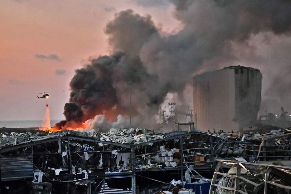 A helicopter puts out a fire at the scene of an explosion at the port of Beirut on Aug 4, 2020.
