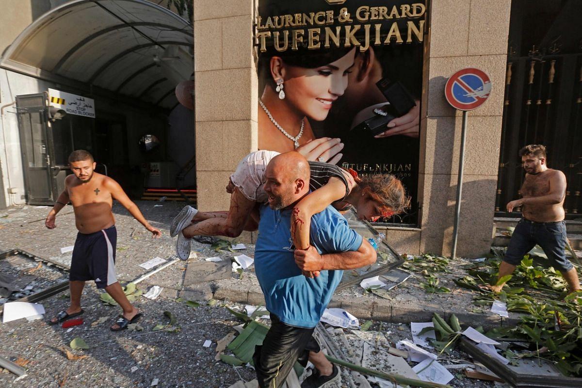 A man carries away an injured girl while walking through debris in the Achrafiyeh district in Beirut on Aug 4, 2020.