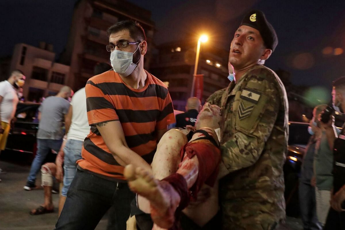 A Lebanese army soldier and a man carry an injured man in the aftermath of an explosion in Beirut on Aug 4, 2020.