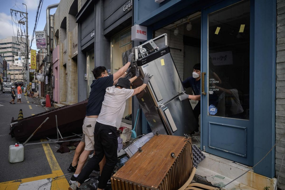 Store workers cleaning up damage to a shop caused by Typhoon Maysak in Busan on Sept 3, 2020.