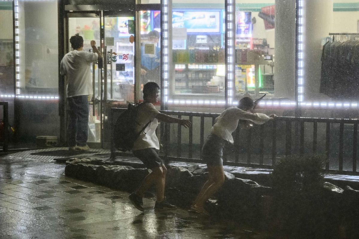 Pedestrians heading to a convenience store for shelter during heavy wind and rain as Typhoon Maysak hit the Haeundae Beach area of Busan on Sept 3, 2020.