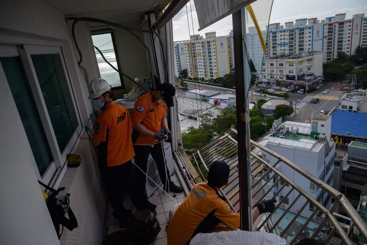 Fire department personnel securing a railing and air-conditioning unit that were left hanging from a shattered window during high winds at an apartment near Gwangalli beach in Busan on Sept 3, 2020.