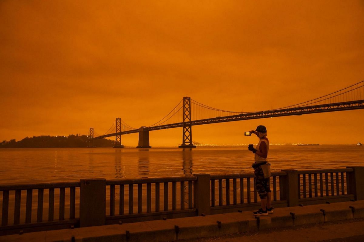 Amy Scott of San Francisco takes in the view from the Embarcadero as smoke from various wildfires burning across Northern California mixes with the marine layer, blanketing San Francisco in darkness and an orange glow on September 9, 2020 in San Fran