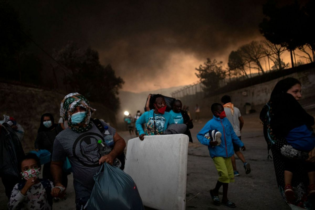 Refugees and migrants carrying their belongings flee a fire burning at the Moria camp on the island of Lesbos, Greece, September 9, 2020. PHOTO: REUTERS