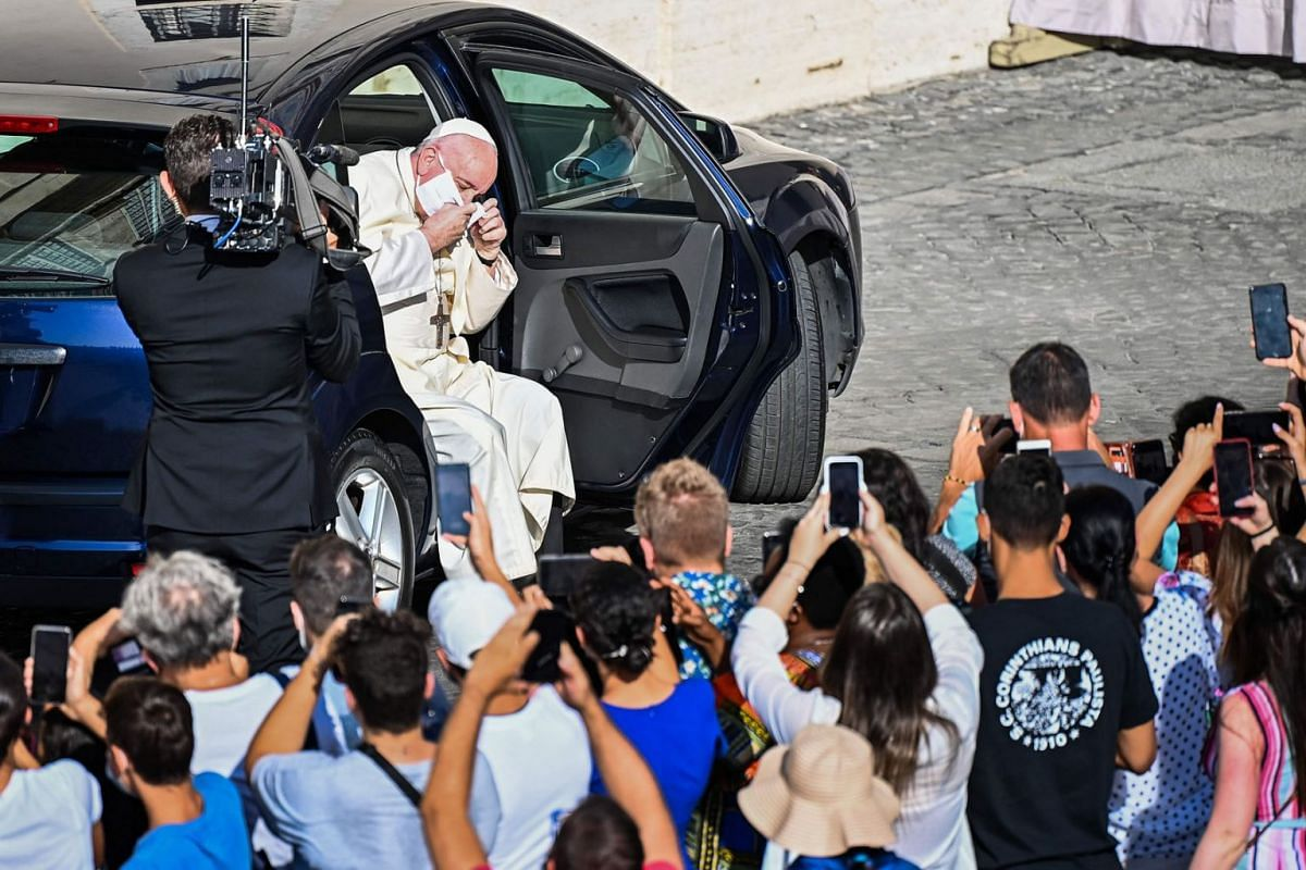 Pope Francis takes off his face mask as he arrives by car to hold a limited public audience at the San Damaso courtyard in The Vatican on September 9, 2020. PHOTO: AFP