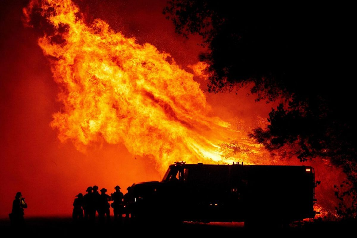 Butte county firefighters watch as flames tower over their truck during the Bear fire in Oroville, California on Sept 9, 2020.