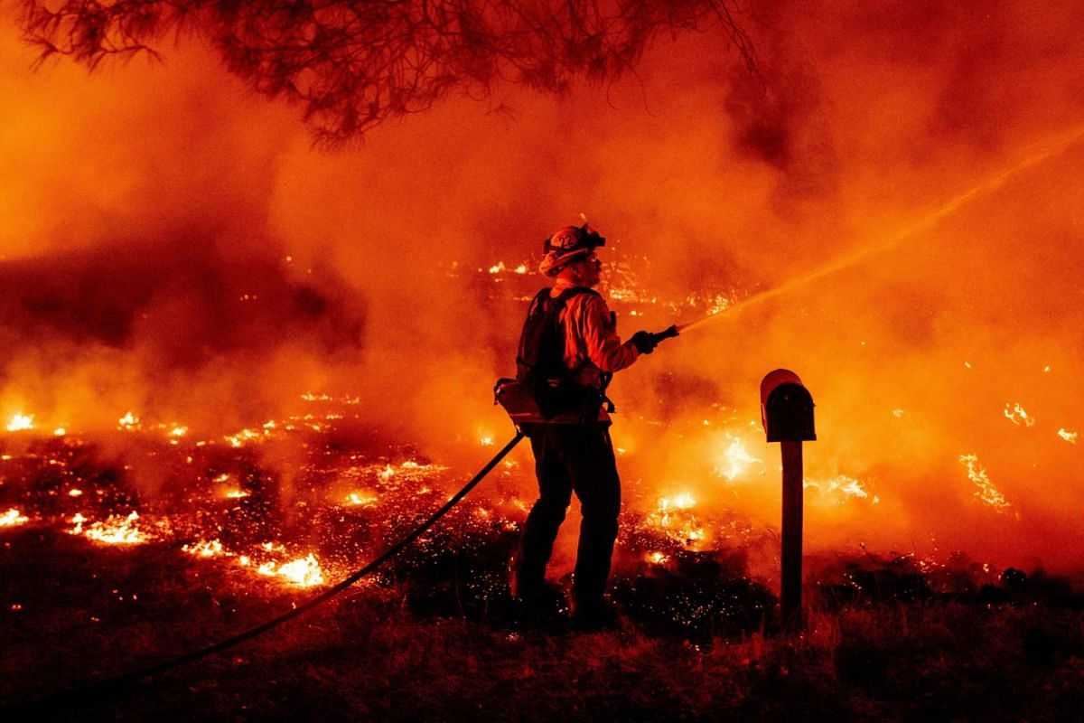 A Butte county firefighter douses flames at the Bear fire in Oroville, California on Sept 9, 2020.