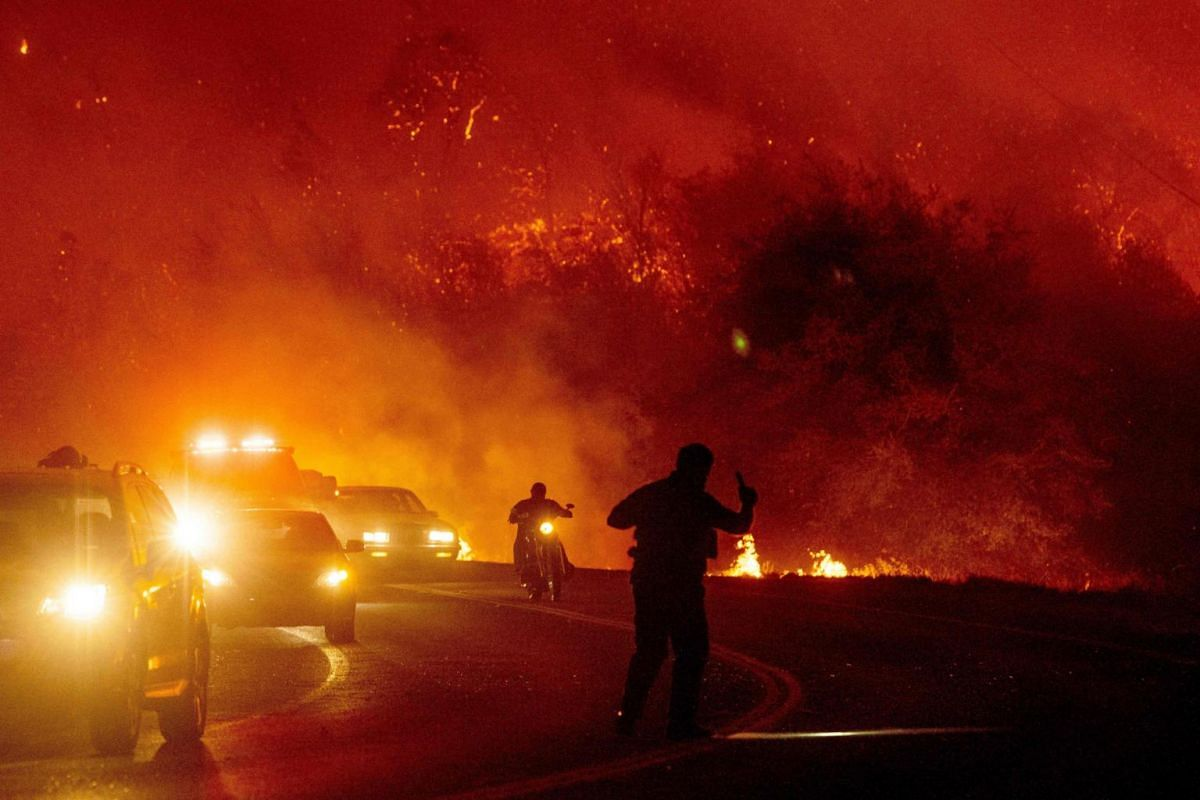 A law enforcement officer guides evacuees down a road surrounded by fire at the Bear fire in Oroville, California on Sept 9, 2020.