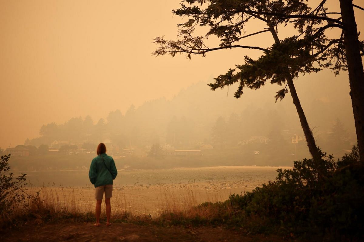 A woman looks at a town by the Pacific Ocean coast as smoke from wildfires covers an area near Yachats, Oregon, US, on Sept 8, 2020.