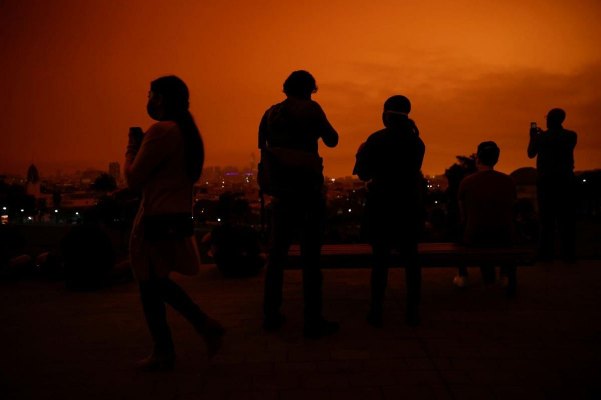 Visitors are seen in Dolores Park under an orange sky darkened by smoke from California wildfires in San Francisco on Sept 9, 2020.