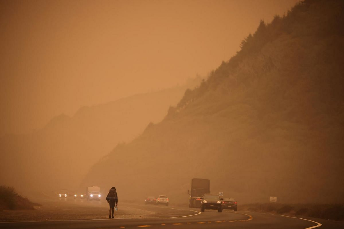A man walks along the Redwood highway by the Pacific Ocean coast as smoke from wildfires covers an area near Orick, California, US, on Sept 9, 2020.