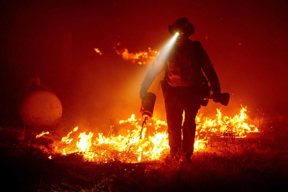 Firefighters cut defensive lines and light backfires to protect structures behind a CalFire fire station during the Bear fire, part of the North Lightning Complex fires in the Berry Creek area of unincorporated Butte County, California on Sept 9, 202