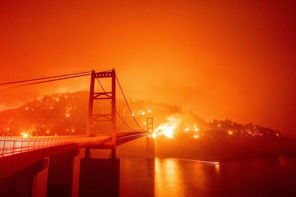 A boat motors by as the Bidwell Bar Bridge is surrounded by fire in Lake Oroville during the Bear fire in Oroville, California on Sept 9, 2020.