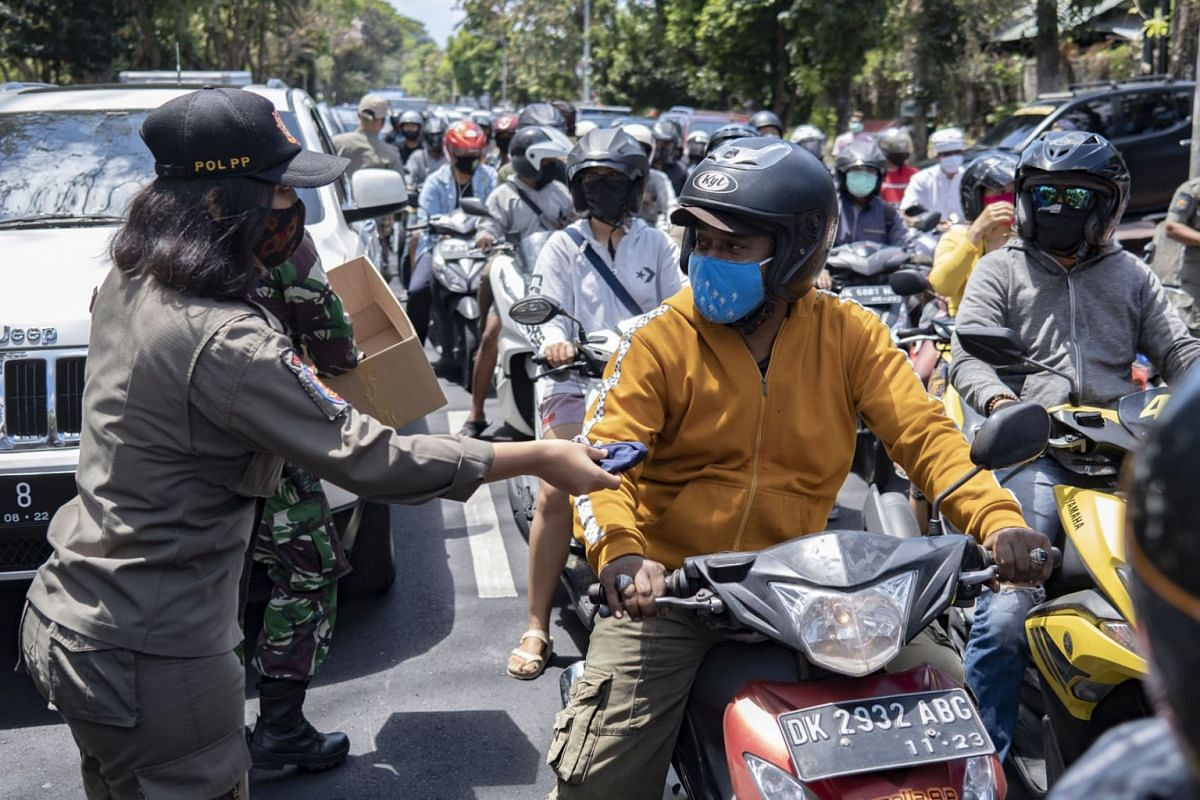 An officer distributes free face mask to people during a mask wearing and public health protocols campaign on a main street in Denpasar, Bali, Indonesia, September 10, 2020. PHOTO: EPA-EFE