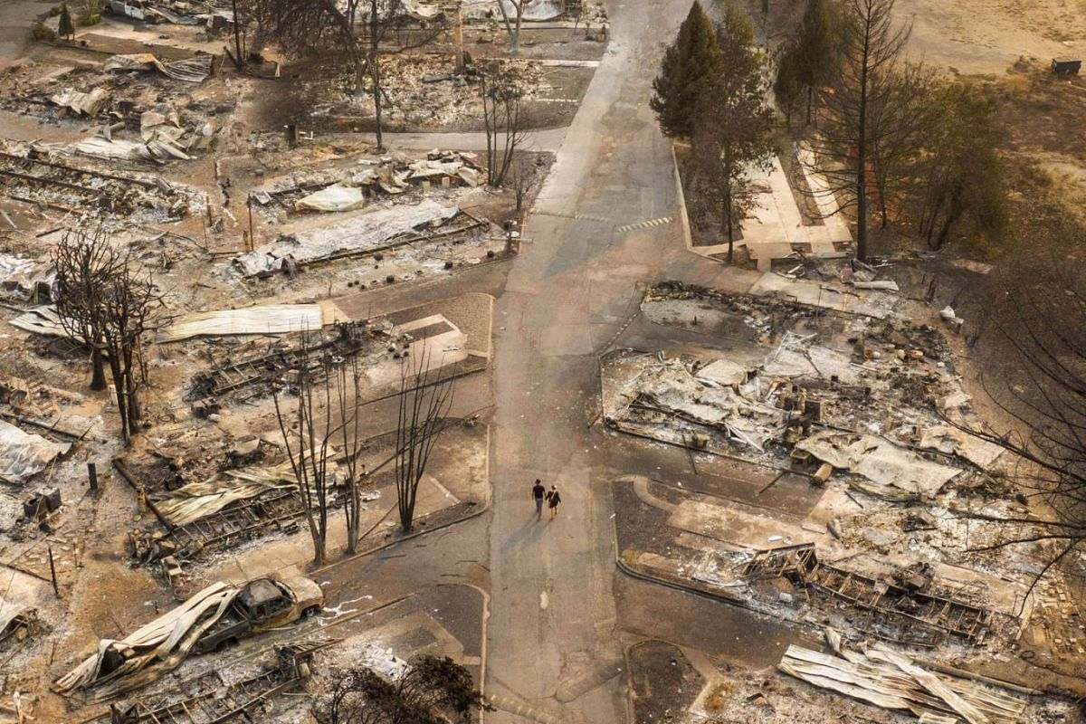 In this aerial view from a drone, people walk through a mobile home park destroyed by fire on September 10, 2020 in Phoenix, Oregon. PHOTO: GETTY IMAGES/AFP