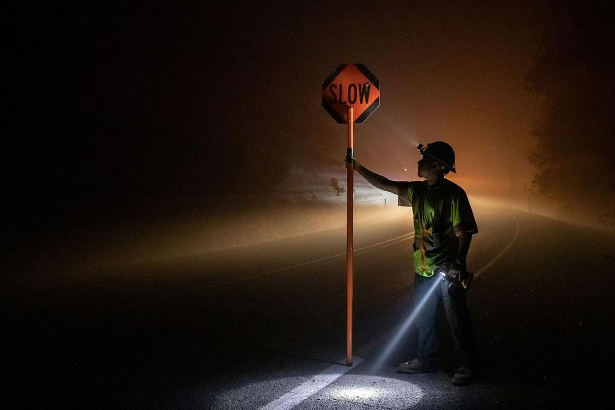 Bryan Alvarez holds a sign for oncoming traffic as utility workers repair power lines in the aftermath of the Obenchain Fire in Eagle Point, Oregon, U.S., September 11, 2020.