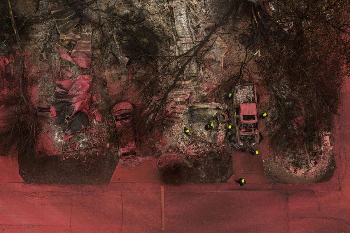A search and rescue team, surrounded by red fire retardant, look for victims under burned residences and vehicles in the aftermath of the Almeda fire in Talent, Oregon, U.S., September 13, 2020.