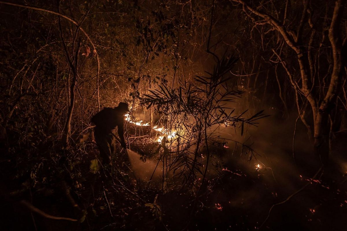 Firefighters spray water to extinguish a fire in the Pantanal wetlands region in Mato Grosso state, Brazil, on Saturday, Sept. 12, 2020. In July, the number of fires burning in the Pantanal, which spans about 210,000 square kilometers, reached the hi