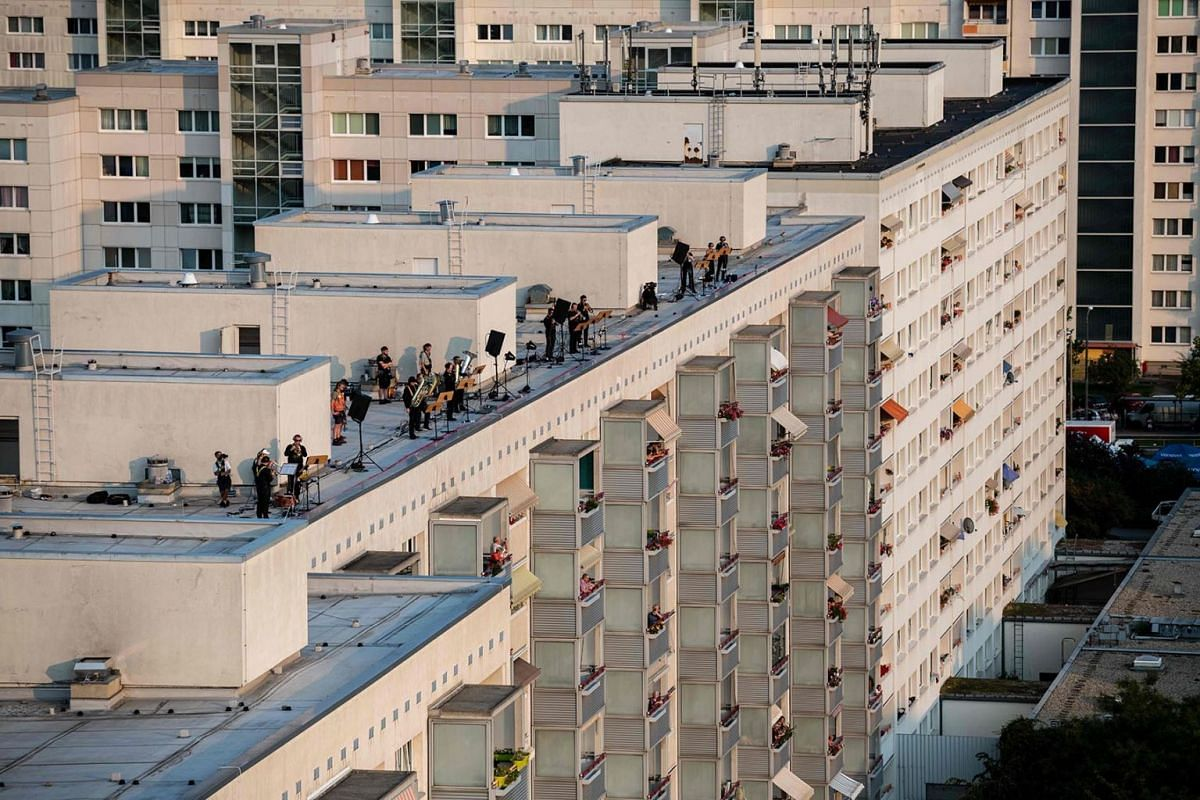 Musicians of the Dresden Sinfoniker orchester play tuba and trumpet during a concert - performance on the roofs high-rise buildings in the Prohlis district of Dresden, eastern Germany, on September 12, 2020.