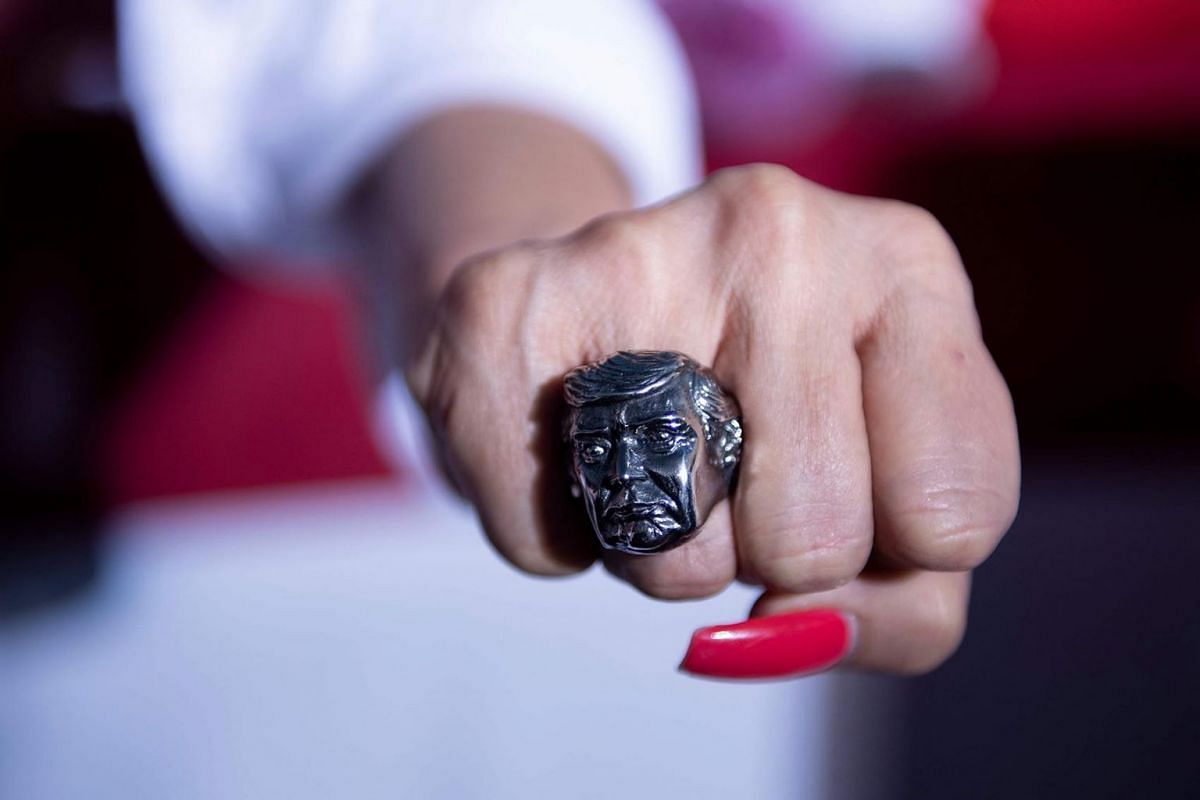 A supporter shows a ring featuring the face of US President Donald Trump during a campaign rally at the Minden-Tahoe airport in Minden, Nevada on Sept. 12, 2020.
