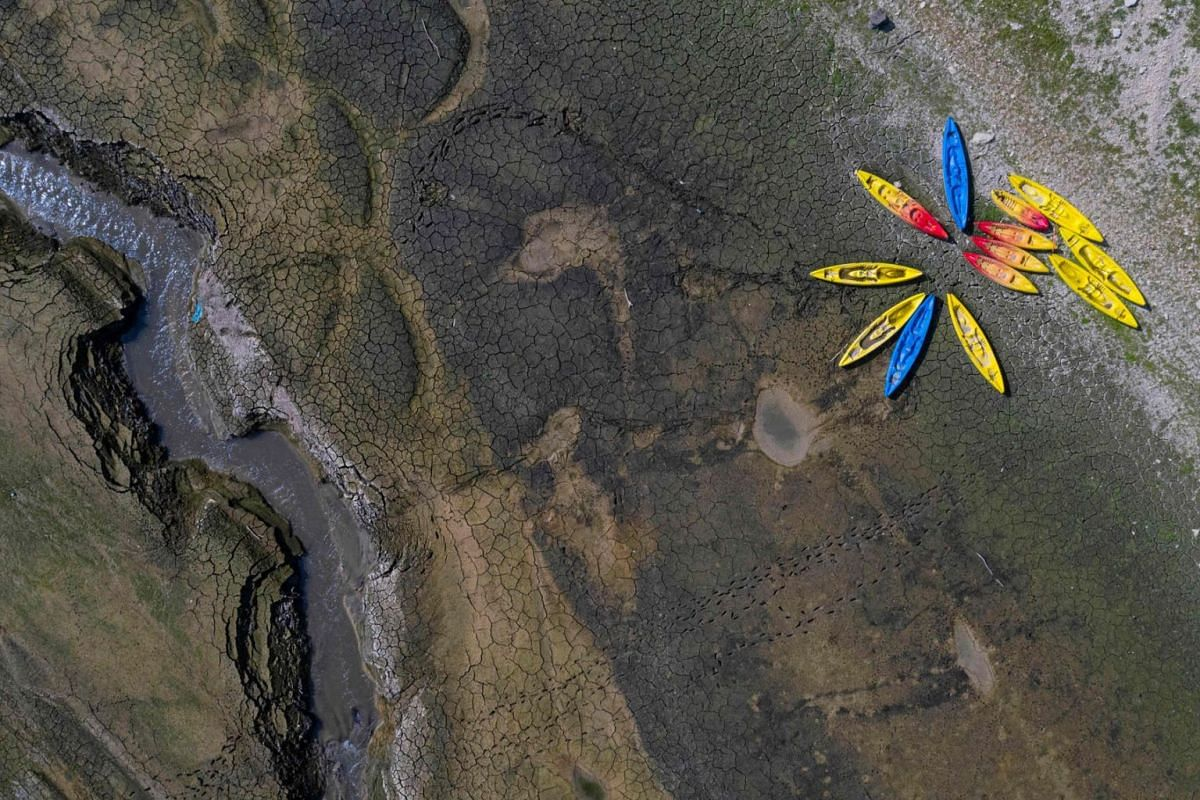 An aerial view shows kayaks near the cracked earth of the bed of the dried-out Doubs river, on September 15, 2020, in Villers-le-Lac, eastern France. A drought in the region has caused the river to be at one of its lowest levels in over a century. PH