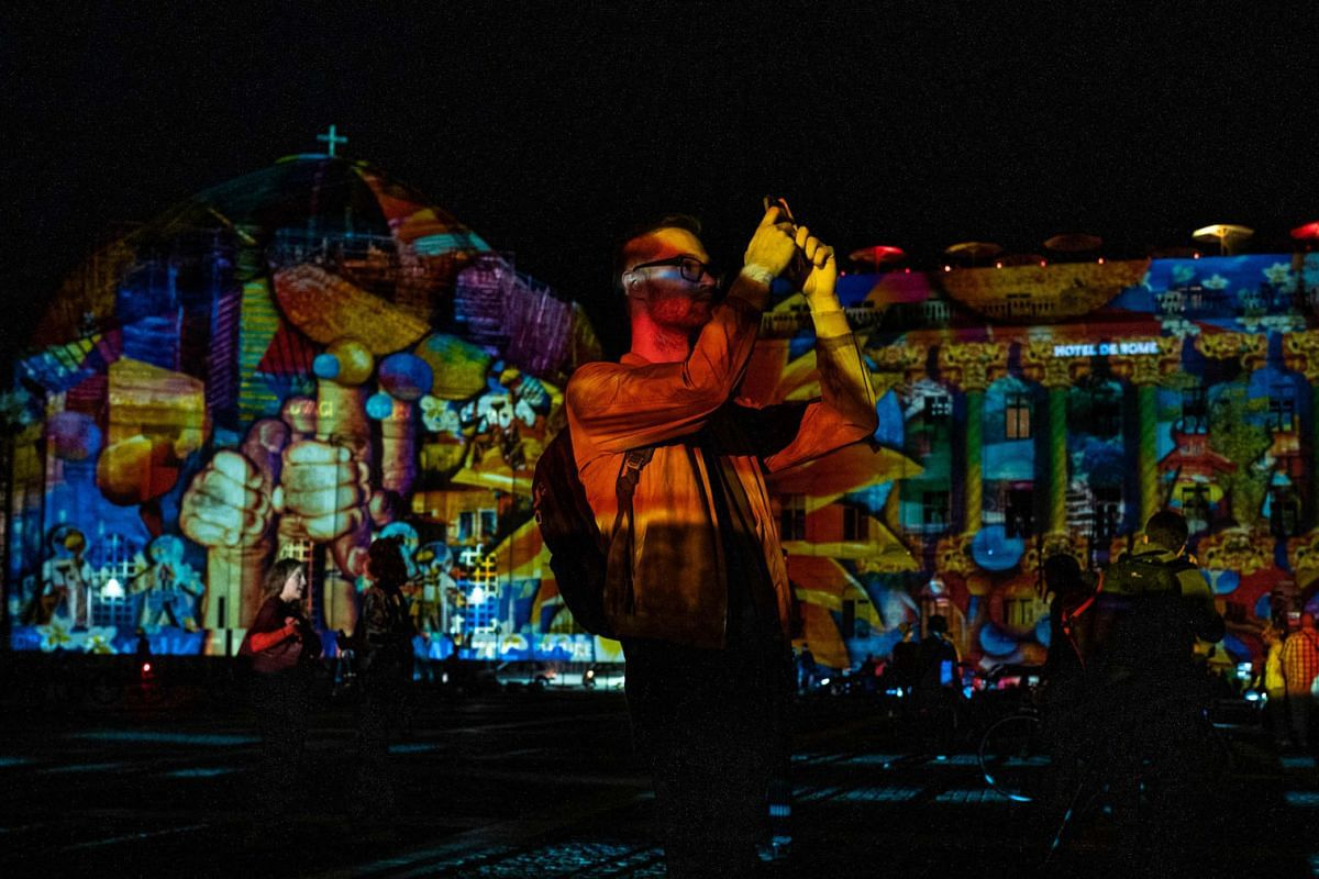 A man takes photographs as he visits the Bebel platz illuminated as part of the yearly Festival of Lights in Berlin on September 14, 2020. PHOTO: AFP