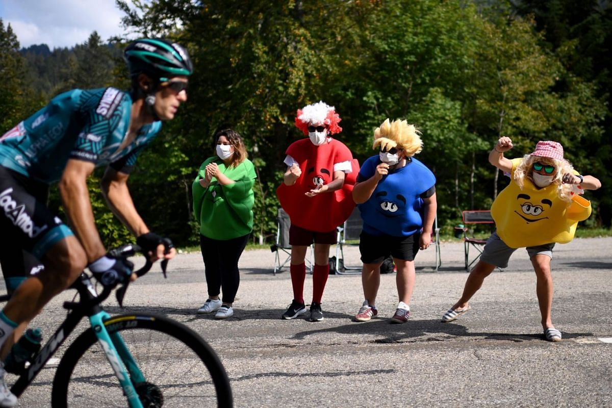 Spectators cheer for Team Vital Concept Cycling Club rider France's Pierre Rolland during the 16th stage of the 107th edition of the Tour de France cycling race, 164 km between La Tour du Pin and Villard-de-Lans, on September 15, 2020. PHOTO: AFP
