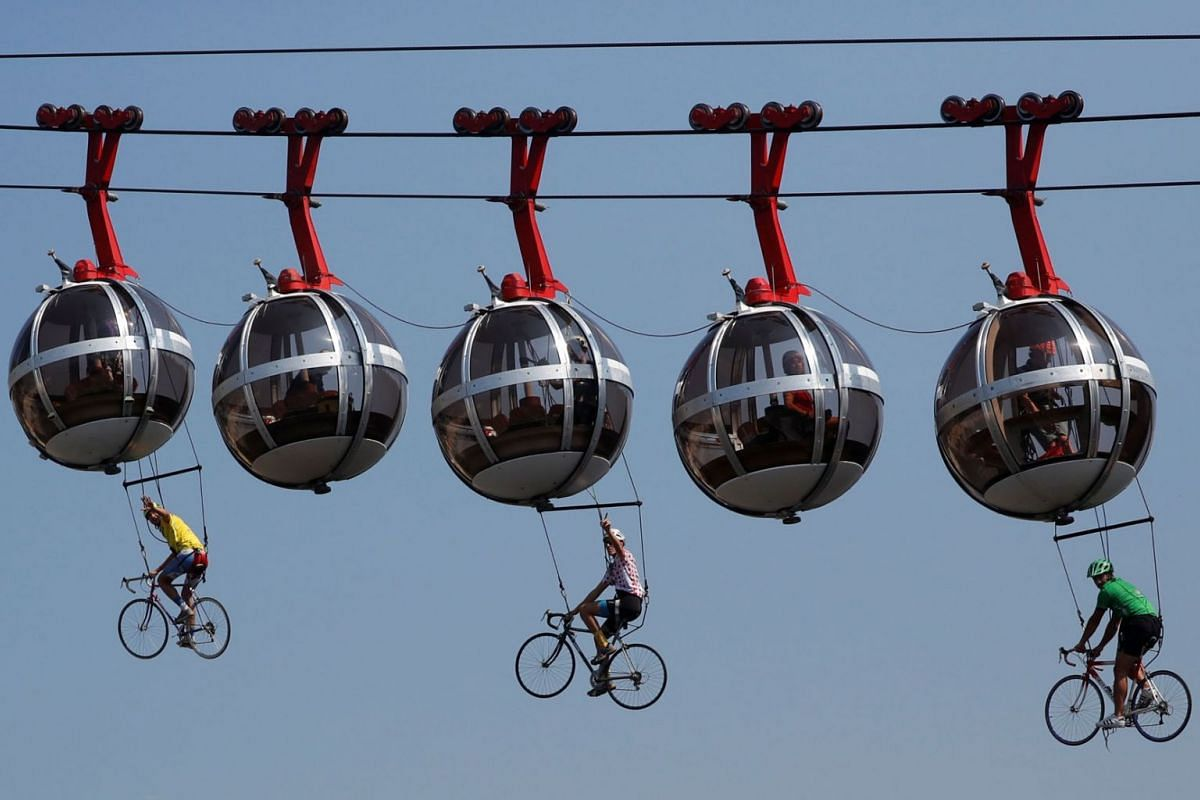 This picture shows cyclists hanging under the Grenoble Bastille cable cars during the 17th stage of the 107th edition of the Tour de France cycling race, 170 km between Grenoble and Meribel, on September 16, 2020. PHOTO: AFP