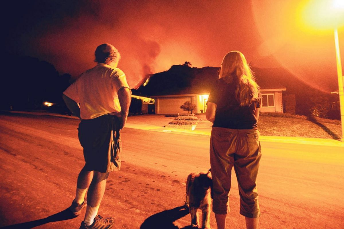 People watch as the Bobcat Fire burns on hillsides behind homes in Monrovia, California on September 15, 2020. PHOTO: AFP