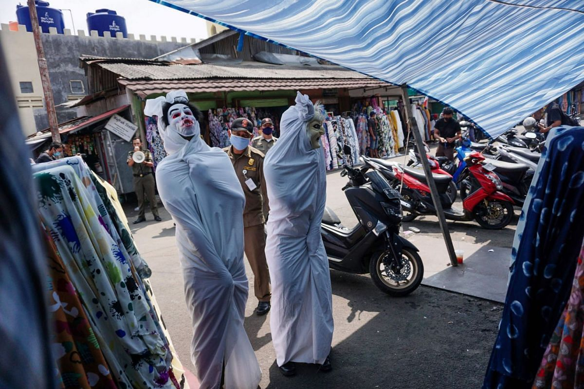 Local government officials wear costumes depicting pocong, one of the famous ghost figures in Indonesia, in an effort to spread awareness about the dangers of the coronavirus,  at a traditional market in Tangerang Banten province, on September 16. P