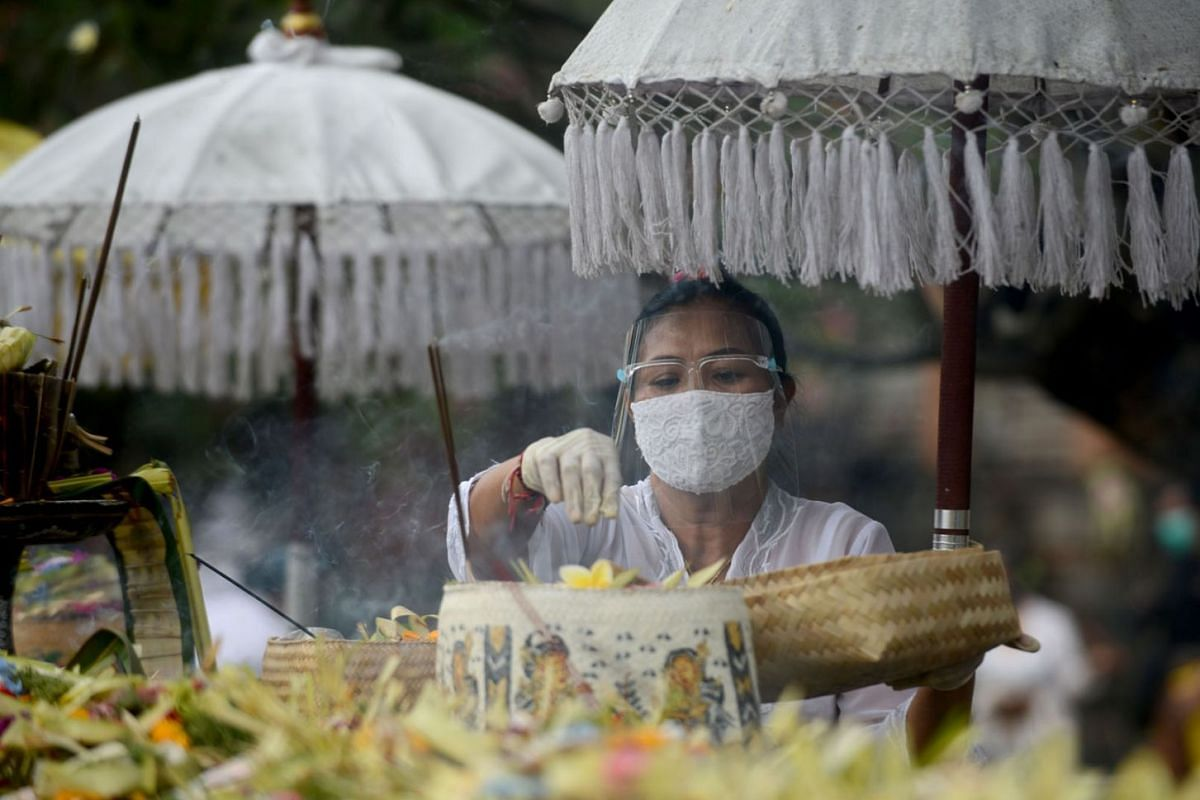 A hindu woman prepares offerings to pray to celebrate the religious festival of Galungan at the Jagat Natha temple in Denpasar, on Bali island on September 16, 2020. PHOTO: AFP