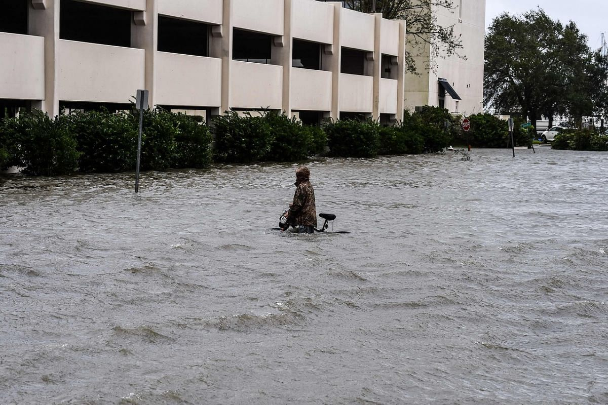 A man walks his bicycle through a street flooded by Hurricane Sally in Pensacola, Florida, on Sept 16, 2020.