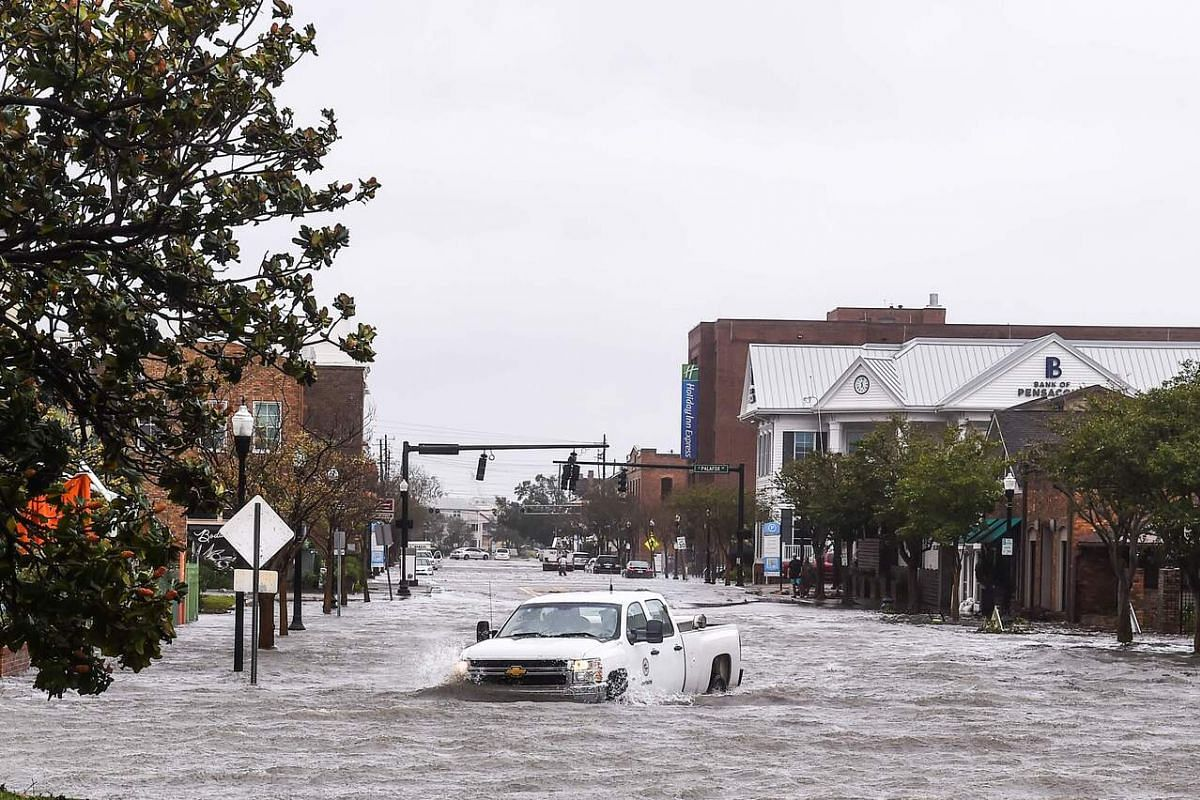 A city worker drives through the flooded street during Hurricane Sally in downtown Pensacola, Florida on Sept 16, 2020.