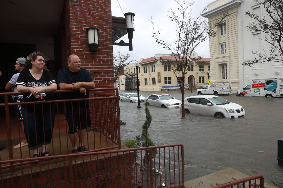 Heather Bordeaux and Mike Bordeaux look out at a flooded street in front of their hotel as Hurricane Sally passes through in Pensacola, Florida, on Sept 16, 2020.