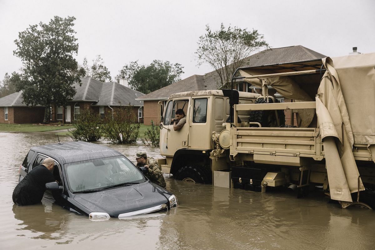 Members of the Florida National Guard rescue local residents from their flooded vehicle on Bristol Park Road in Cantonment, Florida, on Sept 16, 2020.
