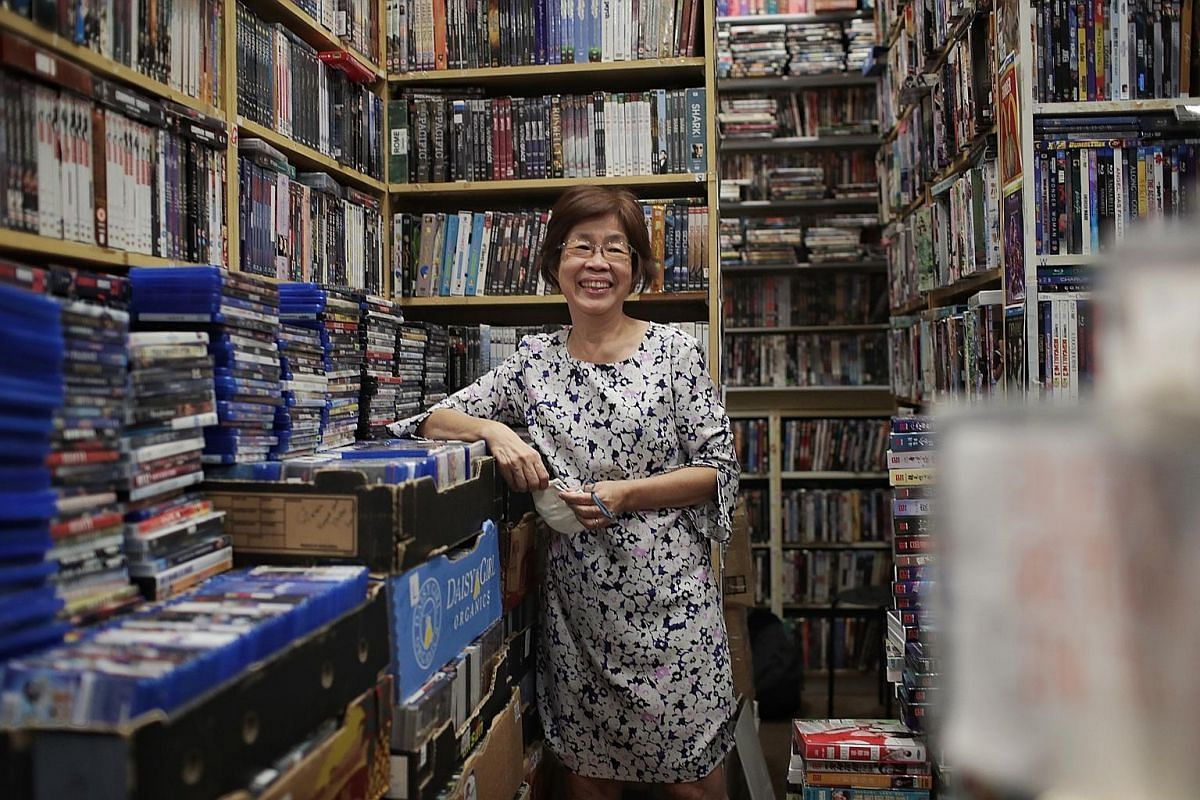 (Above) Madam Laurel Khoo, owner of Rida Video Centre, at the shop on Sept 7. (Right) Madam Khoo's late husband Ooi Kai Peng (standing, second from far right) with staff of Rida Video Centre in Serene Centre, where the video-rental shop was located f
