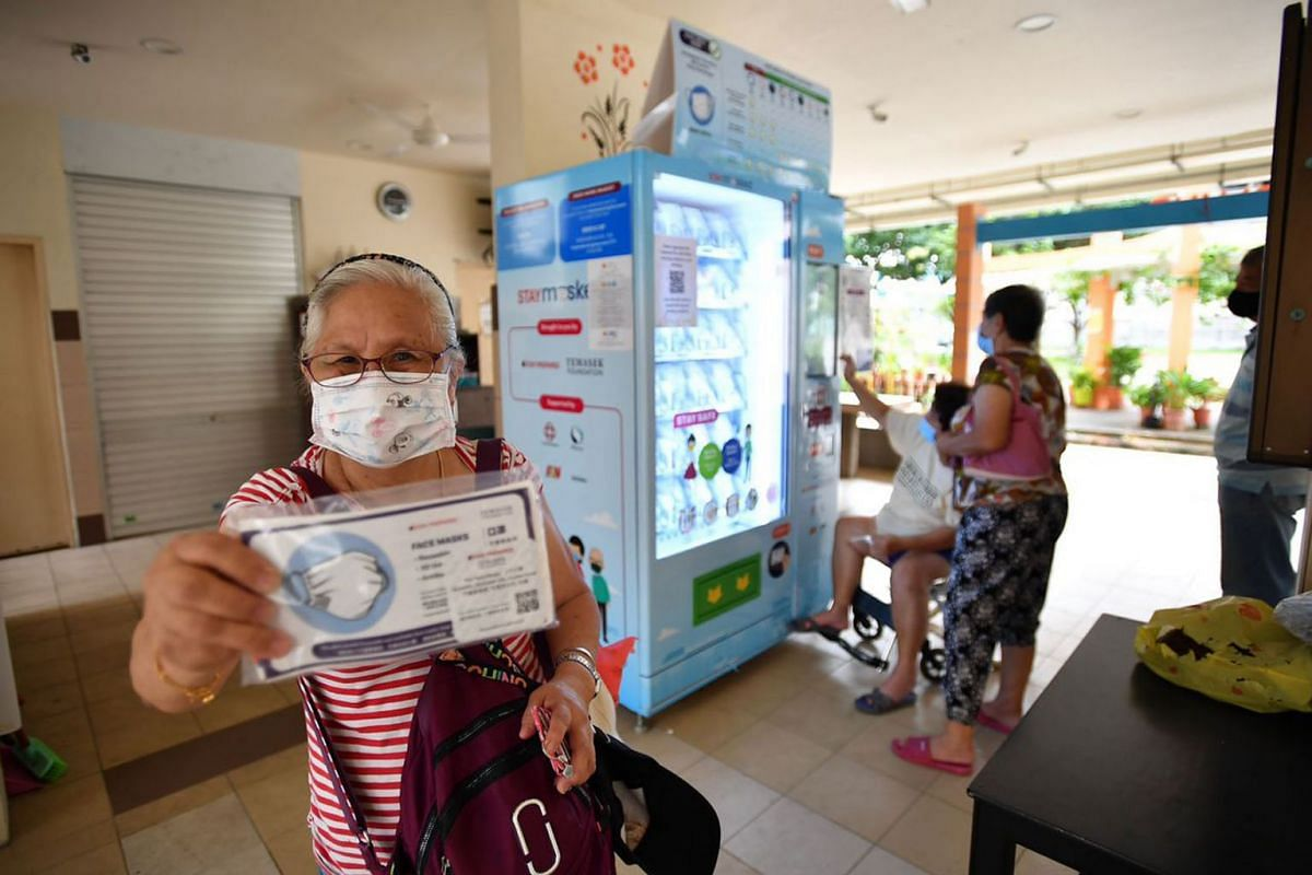 Madam Ng Yang Cher, 68, Housewife, collecting her free mask kit at Tampines Ville RC on September 21, 2020.  The initiative by Temasek Foundation enables Singapore residents to collect two reusable masks each starting from Monday (Sept 21). PHOTO: TH