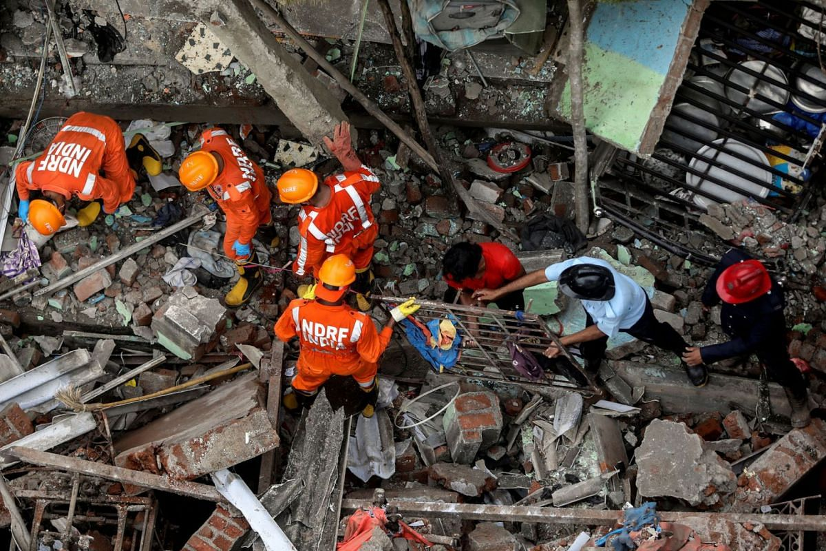 National Disaster Response Force (NDRF) officials and firemen remove debris as they look for survivors after a three-storey residential building collapsed in Bhiwandi on the outskirts of Mumbai, India, September 21, 2020. PHOTO: REUTERS