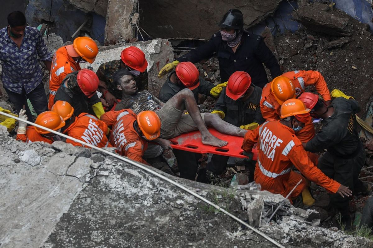 National Disaster Response Force (NDRF) personnel rescue a survivor from the debris of a residential building which collapsed in the early morning, in Bhiwandi, outskirts of Mumbai, India, September 21, 2020. PHOTO: EPA-EFE