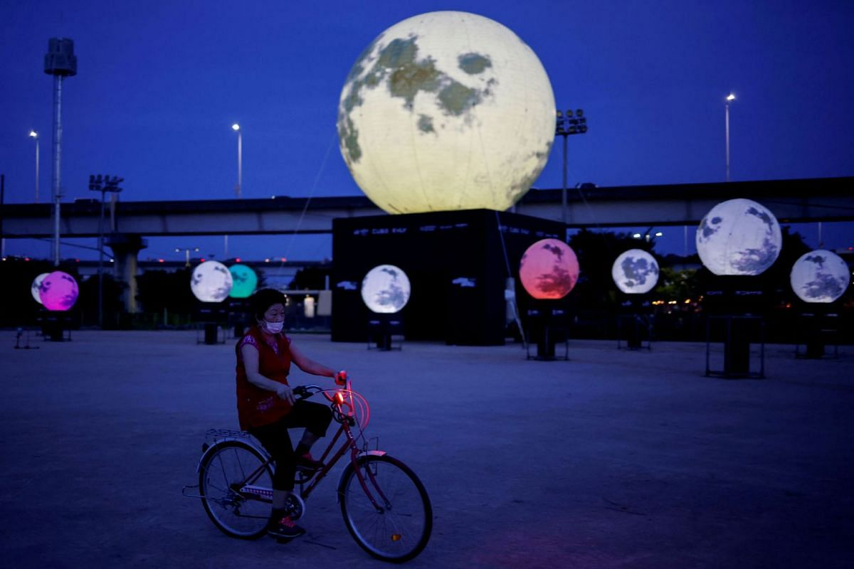 A woman rides a bike next to artificial full moons installed at a park as a wish to overcome the coronavirus disease (COVID-19) and celebrate upcoming Chuseok holiday, the Korean Thanksgiving Day, in Seoul, South Korea, September 21, 2020. PHOTO: REU