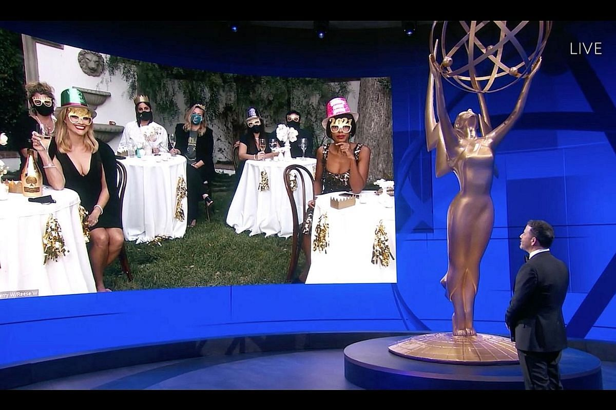 This year's Emmy Awards, hosted by Jimmy Kimmel (above right), is the first major Hollywood ceremony to broadcast live amid the pandemic. The show went largely virtual, with stars, such as Reese Witherspoon (on screen, foreground left) and Kerry Wash