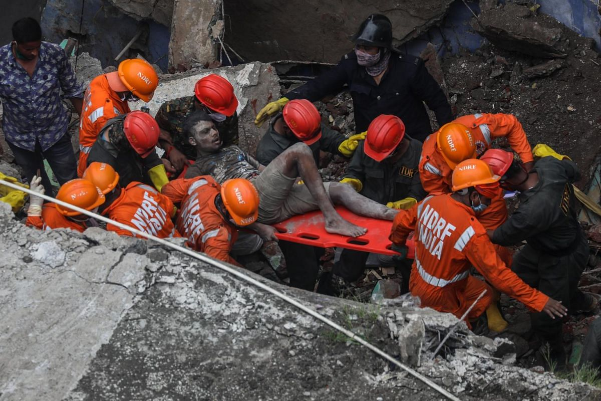 National Disaster Response Force (NDRF) personnel rescue a survivor from the debris of a residential building which collapsed in the early morning in Bhiwandi, on the outskirts of Mumbai, on Sept 21, 2020.