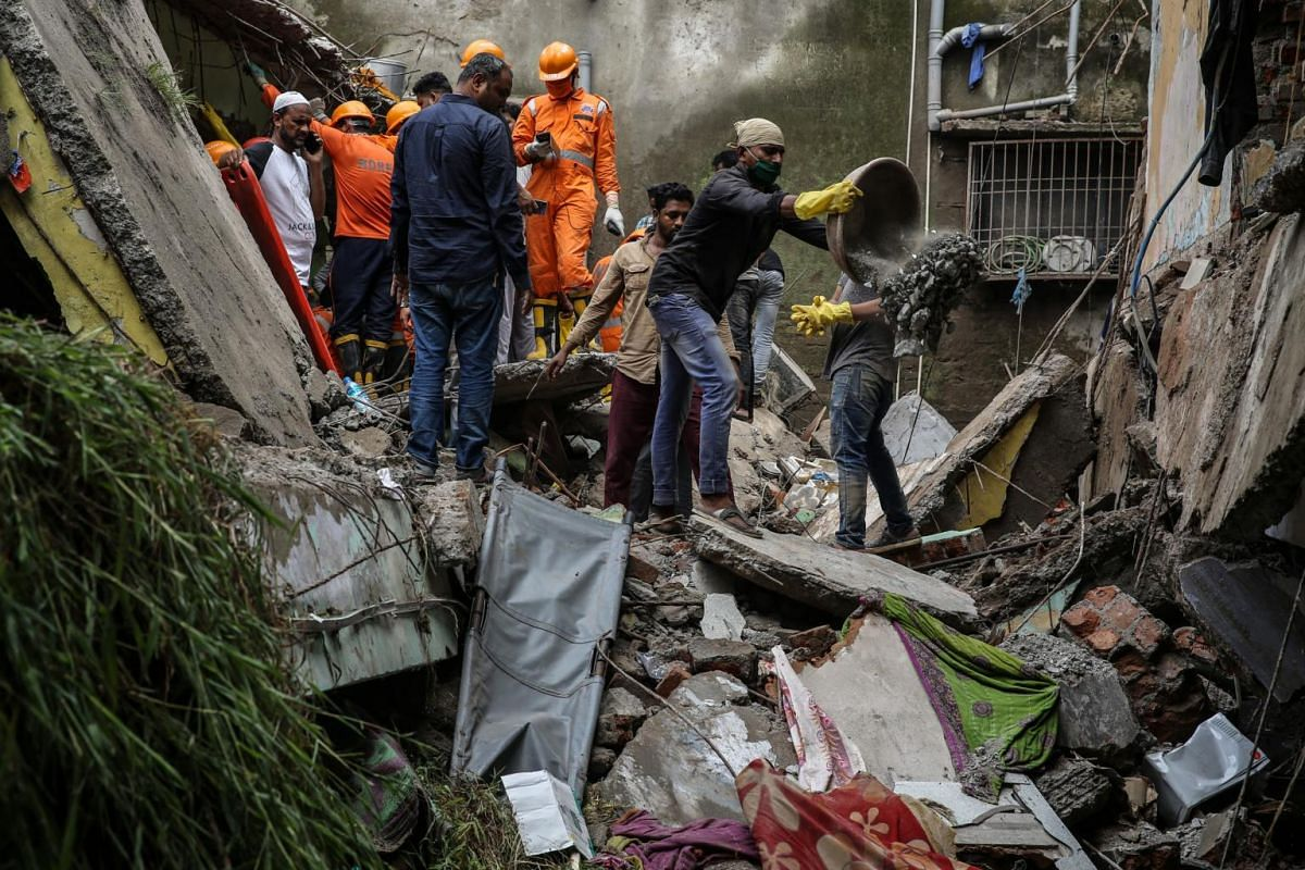 People gather to clear debris in the aftermath of a residential building's collapse in Bhiwandi on Sept 21, 2020.